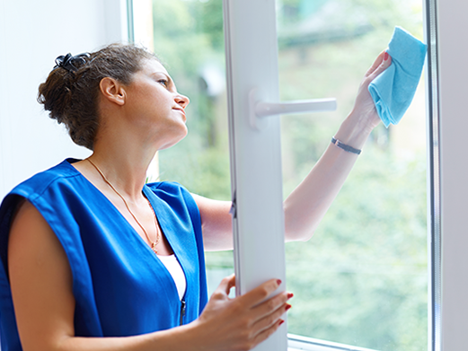 woman cleaning window of a residential house