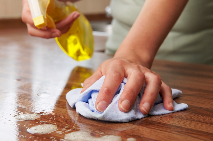Hand providing professional house cleaning services wiping down a wooden service